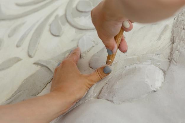 Vrouwelijke handen op het werk kerven een basreliëfpatroon met een instrument