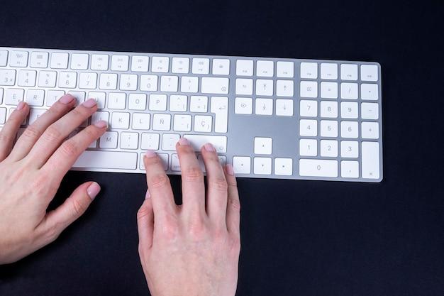 Vrouwelijke handen op het witte en zilveren toetsenbord op zwart