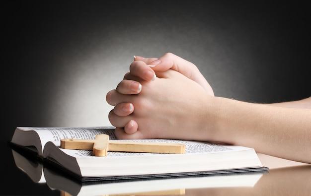Vrouwelijke handen op open russische heilige bijbel