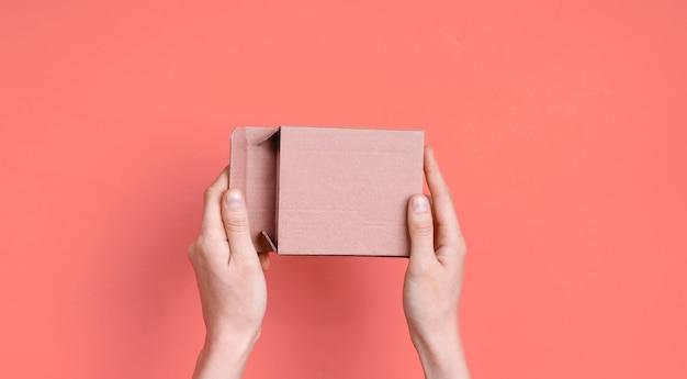 Vrouwelijke handen openen lege kartonnen doos op roze