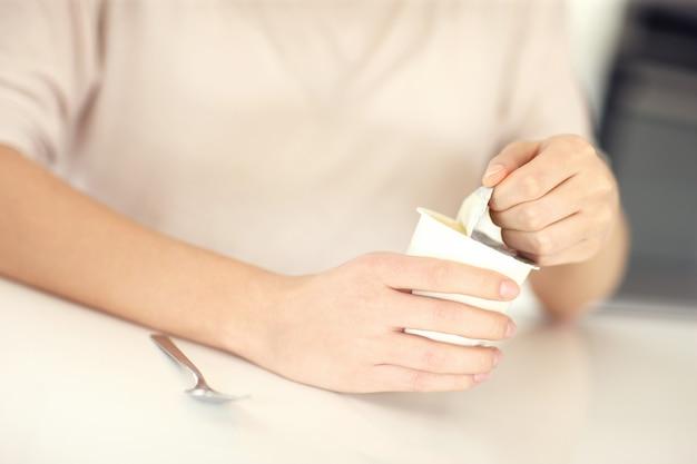 Vrouwelijke handen openen yoghurt in de keuken