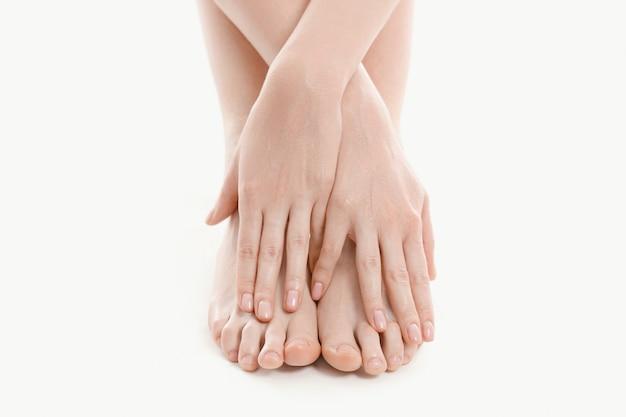 Vrouwelijke handen over de voeten, huidverzorging concept