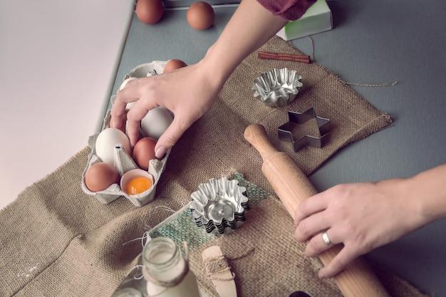 Vrouwelijke handen reiken naar een ei en een deegroller voor het bereiden van koekjes