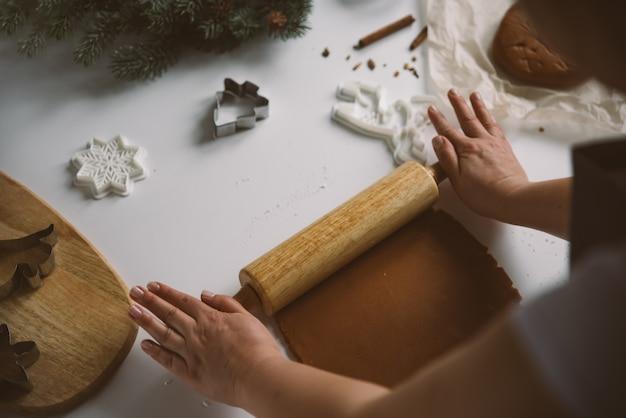 Vrouwelijke handen rollen rauw gemberdeeg uit met een deegroller op een witte tafel