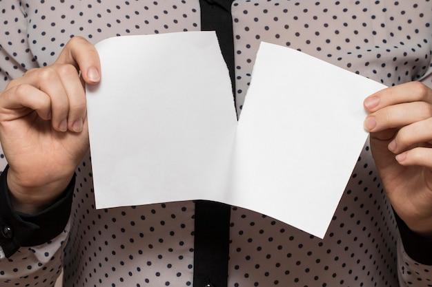 Vrouwelijke handen scheuren een vel papier, close-up.