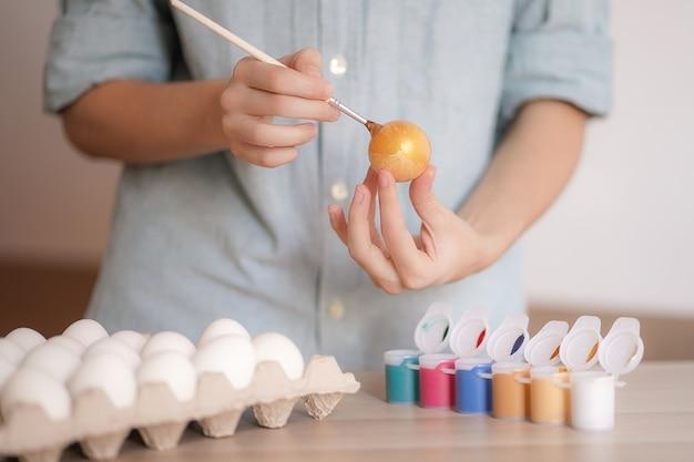 Vrouwelijke handen schildert ei met gouden verf voor pasen