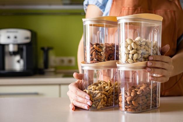 Vrouwelijke handen schort netjes verse, gezonde voedselnoten in glazen potten voor comfortabele opslag