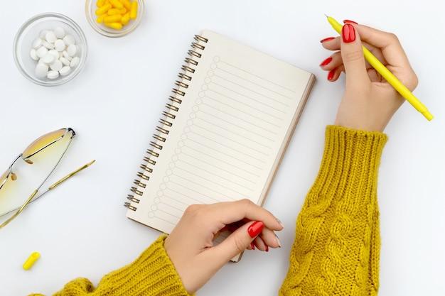 Vrouwelijke handen schrijft in een notitieblok met pillen op tafel