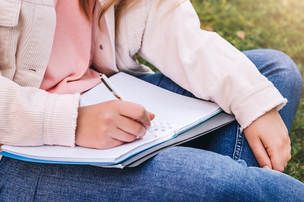 Vrouwelijke handen schrijven in een notitieblok.