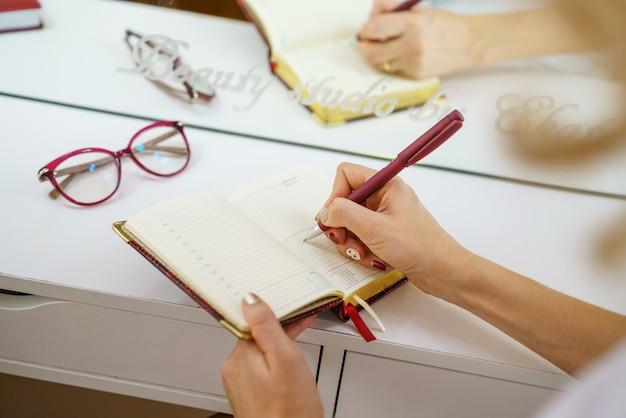 Vrouwelijke handen schrijven met een pen