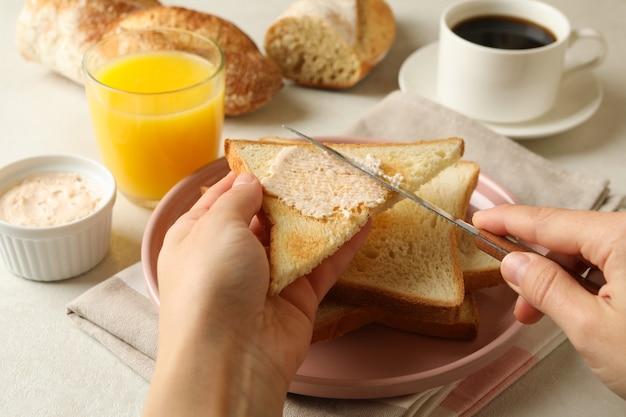 Vrouwelijke handen smeren boter op toastbrood