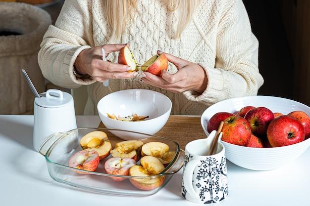 Vrouwelijke handen snijden een appel en bereiden deze voor om te bakken, op de tafel in een witte kom met appels, zelfgemaakt bakconcept voor de vakantie