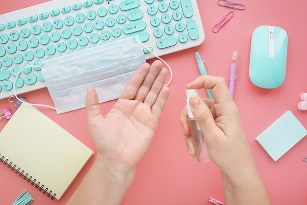 Vrouwelijke handen spuiten hun handen met een ontsmettingsmiddel voordat ze aan het werk gaan op kantoor. hygiënevoorschriften voor pandemieën, epidemieën, griep, coronovirus.