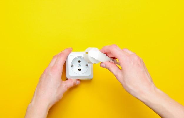 Vrouwelijke handen steken de stekker in het stopcontact. minimalisme. bovenaanzicht