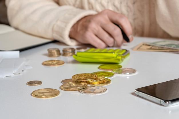 Vrouwelijke handen tellen gegevens btw-belastingen kosten doen papierwerk thuis kantoor tafel, close-up