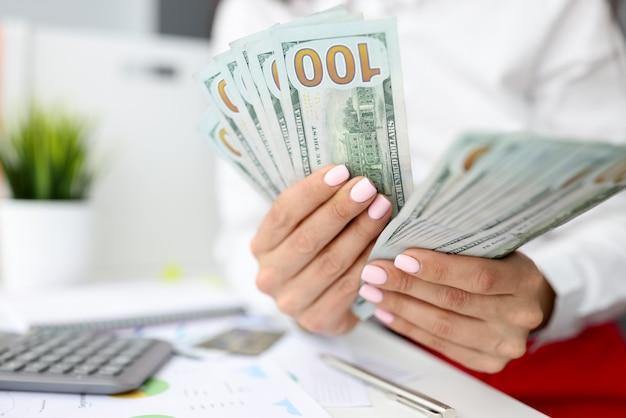 Vrouwelijke handen tellen honderd-dollarbiljetten naast rekenmachine.