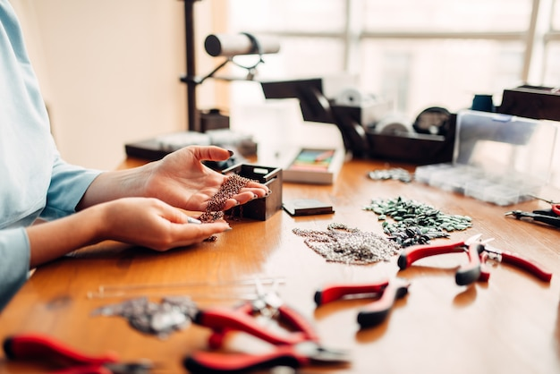 Vrouwelijke handen trekt metalen ketting uit doos