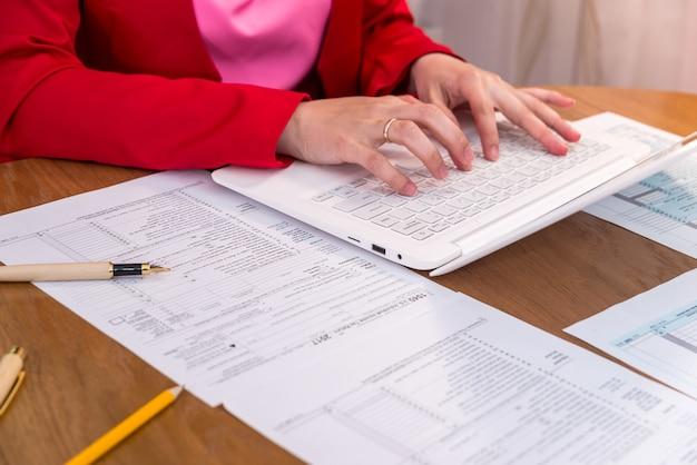 Vrouwelijke handen typen op laptop met formulier 1040
