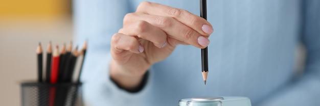Vrouwelijke handen uitsteken potlood in elektronische puntenslijper close-up ontwerp projectontwikkeling