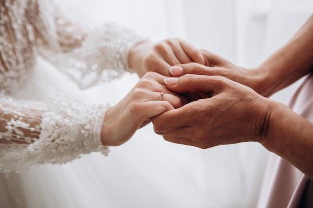 Vrouwelijke handen van bruid en moeder op huwelijksdag in huis