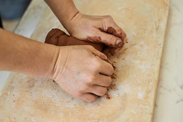 Vrouwelijke handen van de meester kneden rode klei. voorbereiding op het werk in de pottenbakkerswerkplaats.