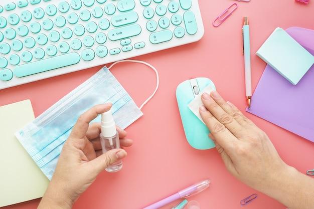 Vrouwelijke handen vegen de muis af met een servet en een speciale desinfecterende oplossing. toetsenbord, klembord, pennen, muis, stickers, paperclips en een medisch masker op het bureaublad.