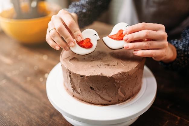 Vrouwelijke handen versieren cake met koekjes in de vorm van vogels. lekker dessert zelfgemaakt koken