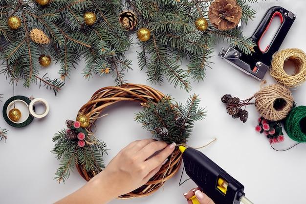 Vrouwelijke handen versieren de kerstkrans met sparren takken met een rode bes en boskegels die...