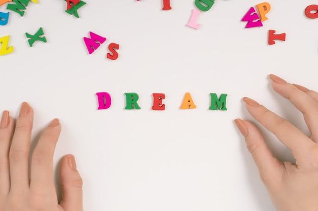 Vrouwelijke handen verspreiden het woord droom van gekleurde letters