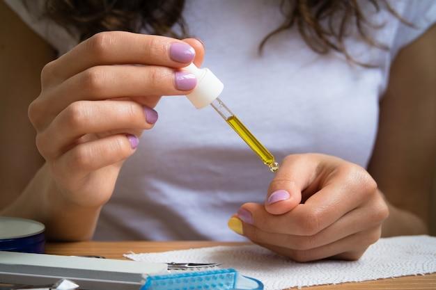 Vrouwelijke handen verzorgen nagelriemen met olie