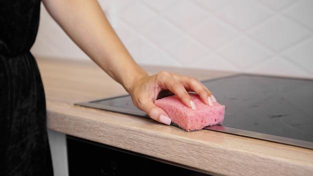 Vrouwelijke handen wassen elektrische kookplaat in de moderne keuken