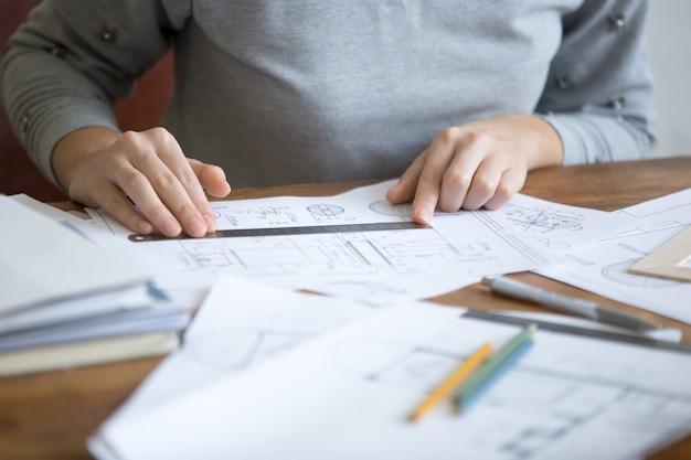 Vrouwelijke handen, werken met een liniaal en een tekening