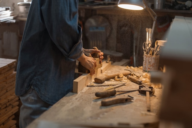Vrouwelijke handen werken met hout. het concept van handmatig werk. levensstijl van ambachtslieden. houten werkplaats