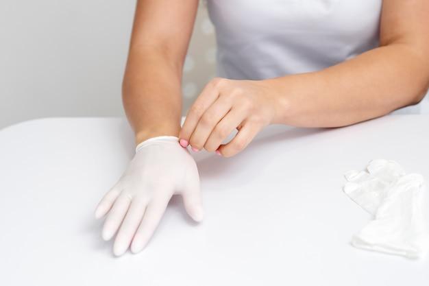 Vrouwelijke handen zetten beschermende handschoenen