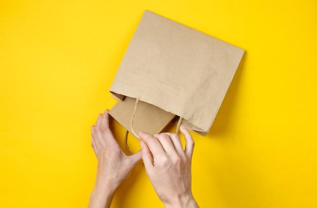 Vrouwelijke handen zetten een kartonnen doos in een papieren zak op een gele. bovenaanzicht