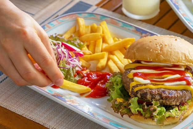Vrouwelijke handenvingers die en gebraden frieten in tomatenketchup houden druipen op een plaat met hamburger