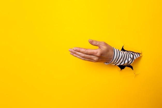 Vrouwelijke handpalm in een gat op gescheurd