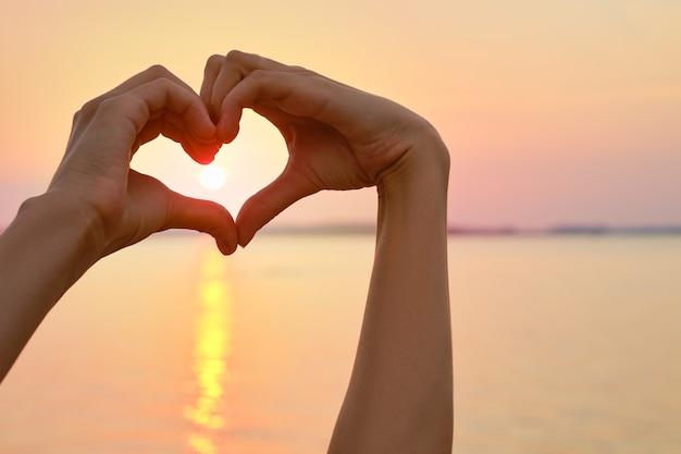 Vrouwelijke handpalmen vormen de vorm van het hart met zonsondergang op de achtergrond