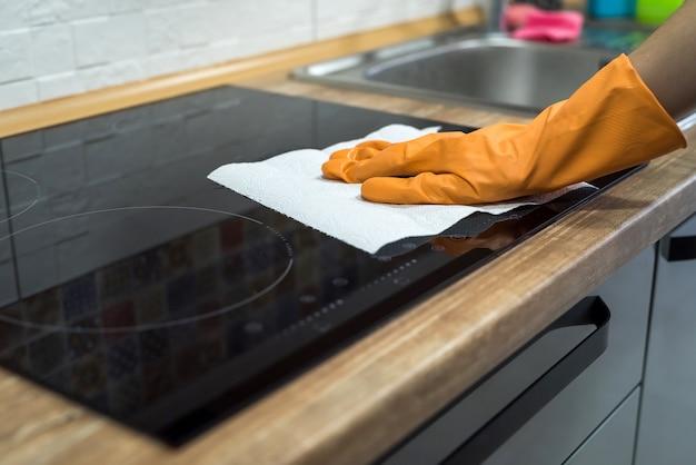 Vrouwelijke handreiniging met spons en wasmiddel moderne kookglazen elektrische kookplaat