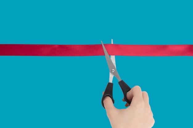 Vrouwelijke handschaar knipt een rood lint. isoleer op een blauwe achtergrond.