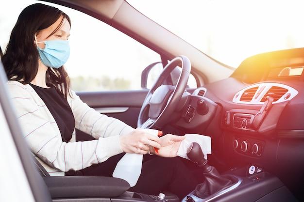 Vrouwelijke handspray ontsmettingsmiddel en antiseptische vochtige doekjes voor het desinfecteren van auto tijdens corona-virus.