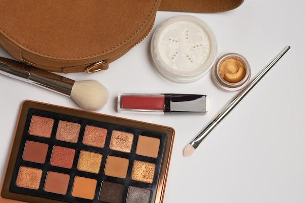 Vrouwelijke handtas met losse poeder, penseel en oogschaduwpalet op een grijze achtergrond