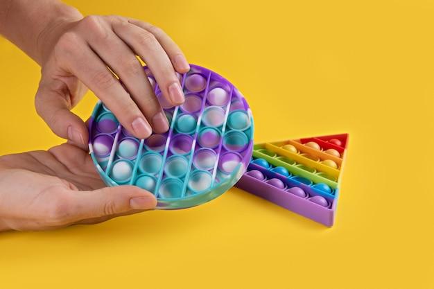 Vrouwelijke hans met pastelkleurige ronde popit speelgoed antistress