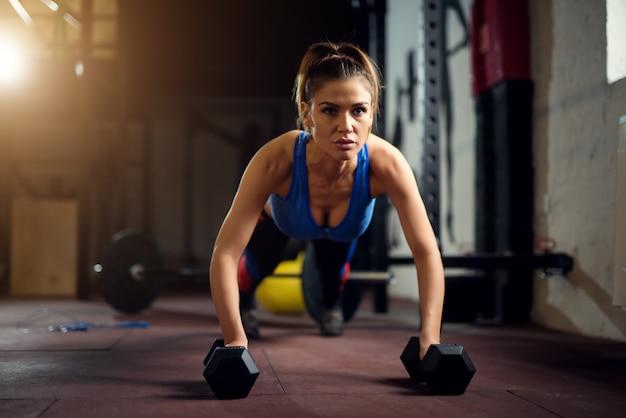 Vrouwelijke harde werkoefening. sterke vrouw op sportschool.
