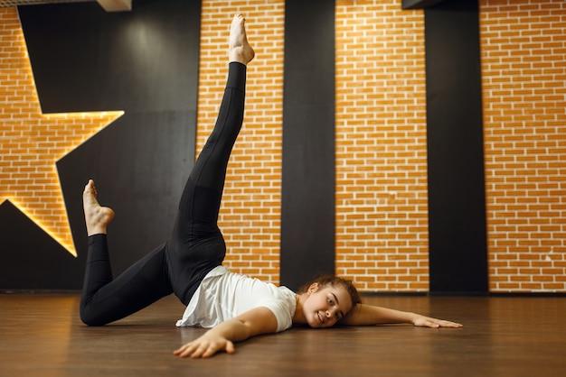 Vrouwelijke hedendaagse dansartiest, lichaamsflexibiliteit. danseres op training in de klas, modern ballet, elegantie dansen, rekoefening