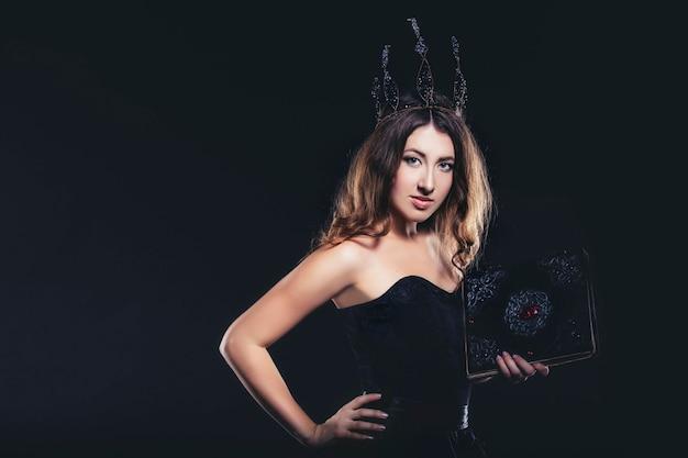 Vrouwelijke heks in zwarte jurk en kroon op zwarte achtergrond