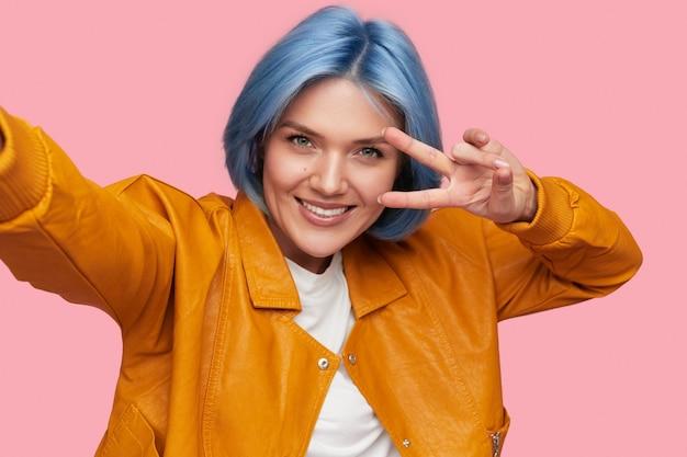 Vrouwelijke hipster gebaren v-teken