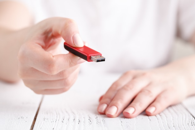 Vrouwelijke hold flash drive in de hand op witte tafel