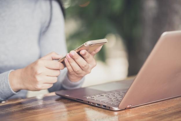 Vrouwelijke holdingssmartphone die bericht met bevestiging krijgen die transactie op laptop computer maken
