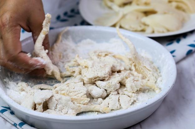 Vrouwelijke home chef hand coating oesterzwam met bloem. kookstap krokant gebakken oesterzwam of jamur krispi maken. oesterzwam bedekt met gekruide bloem en depp fried.